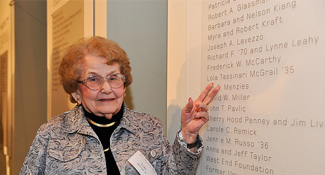 Lola T. McGrail '35 points to her name on the Founders Circle tribute wall in the Campus Center.